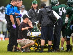 Green Hope quarterback Chris Tutwiler is greeted by teammates as he is helped onto a stretcher after being injured at the HighSchoolOT Jamboree.