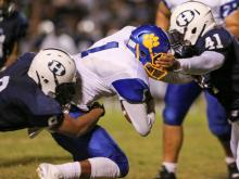 Hillside's Aaron Mccullough (8) and Hillside's Laurence Fogg (41) tackle Dudley's Hendon Hooker (1) during Dudley High Schools defeat of Hillside High School 12-9 on Friday September 12,  2014, Durham NC.  (Photo: Karl Fisher / WRAL contributor)