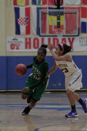 Myers Park's Aliyah Mazyck dripples around East Wake's S. Richardson at the HighSchoolOT.com Holiday Invitational Wednesday night at Cary Academy.  Myers Park defeated the Warriors 65-60 (photo by Wes Hight).