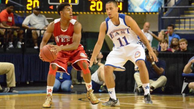 East's T.J. Evans plays defense on West's Devonte Boykins.