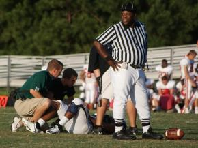 Southeast Raleigh sports medicine staff members work on an injured Bulldog player during a game against Sanderson on Aug. 29, 2009.