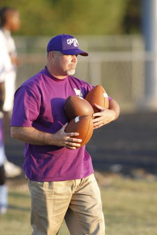 Broughton's head coach Chris Martin gathers up some game balls as Broughton wins big 52-26 over Millbrook Friday Sept.24, 2010 at Millbrook high school in Raleigh, NC.