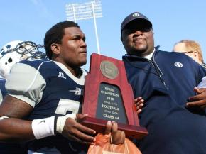 #25 Shyeim Stephens and Head Coach Antonio King share the state championship trophy after Durham Hillside High School's 40-0 victory over Davie County High School to win the NCHSAA 4-A Football Championship on Saturday, Dec. 11. (photo by Will Okun)