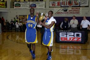 Garner's  Cameron Redd (#44) and Garner's  Gavin Wilson (#32) carry the winners trophy after Garner defeated St. Raymond 75 to 63 in the American Airlines bracket during the 2011 HighSchoolOT.com Holiday Invitational Basketball tournament Friday December 30, 2011.