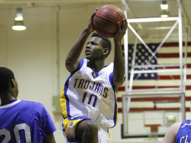 Garner's Julius Barnes (10) gets up for a shot in the lane over Clayton's Rodney Moore (20). Garner won the the Greater Neuse River Conference Tournament Championship played at Garner High School Friday, February 17, 2012 beating Clayton 70-68. Photo by Dean
