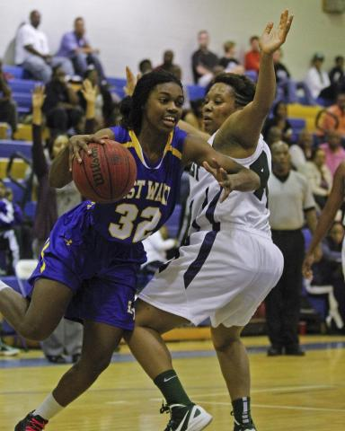 East Wake's Shakerrya Morrison (32) drives around Southeast Raleigh's Kaleisha Moore (40) in 1st quarter action.  Southeast Raleigh defeated East Wake 64-47 to win the Greater Neuse River Conference Tournament Championship Friday night February 17, 2012 played at Garner High School. Photo by Dean Strickland OD.