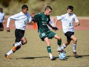 Cole Dixon (16) splits defenders.  Green Hope High School defends their state title with a 2 to 0 final score.