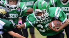 A Cary Chargers player runs the ball against the Apex Cougars in a Pop Warner football game at Cary High School on Saturday, Oct. 19, 2013. (Photo by: Nick Stevens)
