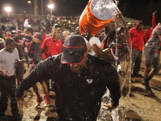 Head Coach Adrian Jones receives a celebratory shower as Southern Durham defeats Wilson Hunt 38 to 10 in the 3AA regional finals of the 2013 NCHSAA football championship Friday December 6, 2013.(Photo by Jack Tarr)