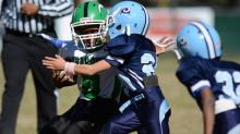 A Cleveland Rams player tackles a Cary Chargers player in a Mitey Mite Pop Warner football game. (Photo By: Nick Stevens)
