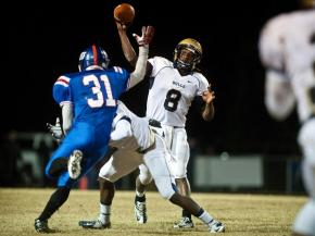 E.E. Smith's Phillip Bell passes the ball as Scotland's Tim McNeill comes at him during the first quarter of Friday night's game at Scotland High School in Laurinburg.