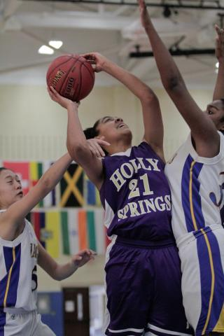 Holly Spring's Hadiya Howard (21) attempts to take a shot as she is fouled by Cary Academy's Szu-In Lim at the HighSchoolOT.com Holiday Invitational Wednesday morning at Cary Academy.  The Chargers fell to the Holly Springs Hawks 62-49 (photo by Wes Hight).