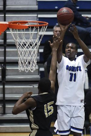 Clayton High's Gary Clark (11) get off a short jump shot over Knightdale's Rashad Allen-Shabazz (15). Clayton defeated Knightdale High 75-74 in the Greater Neuse River conference game played at Clayton High School, January 18, 2013. Photo by Dean Strickland, OD.