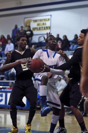 Clayton's Anthony Gaskins (5) gets between Knightdale defenders on his way to the basket. Clayton defeated Knightdale High 75-74 in the Greater Neuse River conference game played at Clayton High School, January 18, 2013. Photo by Dean Strickland, OD.