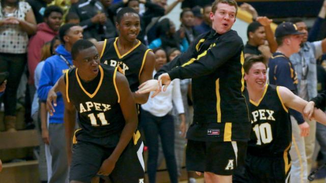 Majid Raji (11) and Apex celebrate the game winning shot. Apex advanced to the 4th round by defeating Northern 65-64 on February 28, 2014 in Durham, North Carolina. Photo by: Jerome Carpenter