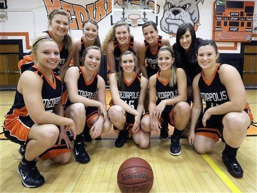 In this Feb. 1, 2013 photo, members of the Mediapolis High School Girls Basketball team pose for a photo in Mediapolis, Iowa. The dynamic of one of Iowa's best high school basketball teams is defined by an extraordinary coincidence of five sets of sisters.(AP Photo/Seth Perlman)